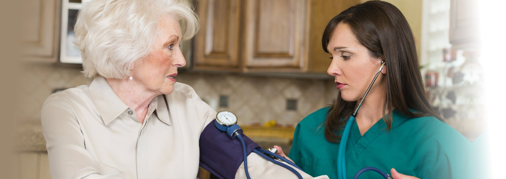 Nurse looking worried while checking the blood pressure of a senior
